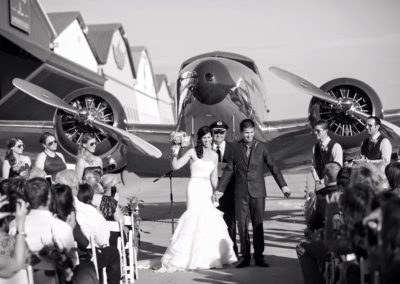 wedding at cal aero in front of bi plane on tarmac at hanger